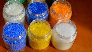 Små korn i olika färger i små plastburkar. blåa, gula, vita gröna små korn.