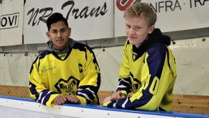 Lucas Nordgren och Linus Böling, hockeyspelare i Närpeslaget Krafts C-juniorer, står i ishallen vid sargen i gula spelskjortor