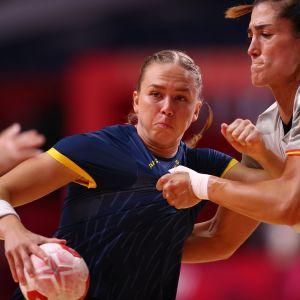 Sveriges Jenny Carlson håller i bollen och kämpar mot en motståndare i premiärmatchen mot Spanien i OS i Tokyo.