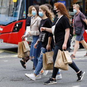 Människor i munskydd går på Oxford Street i London.