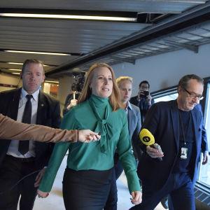 En kvinna marscherar bestämmt genom en korridor med säkerhetsteam och journalister som sticker fram mikrofoner.
