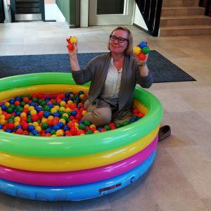 Lasten puhallettavassa monivärisessä uima-altaassa pallomerellisiä palloja ja professori Kirsi Vainio-Korhonen istumassa niiden keskellä.