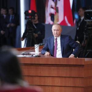 Vladimir Putin sitter bakom ett skrivbord under sin årliga presskonferens 2017.