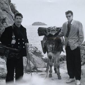 Kaksi miestä mustavalkoisessa kuvassa Kreikan saaristossa aasi välissään