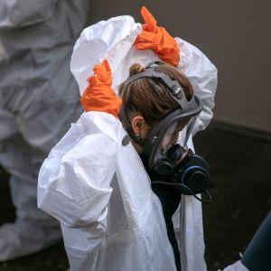Person i vit skyddsdräkt och skyddmask. Med orange handskar på händerna håller personen på att ta av sig skyddsdräkten.