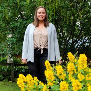 Leende kvinna bakom gula blommor.