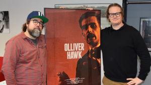 Oskar Forstén och Arthur Franck poserar vid filmaffischen till Olliver Hawk.