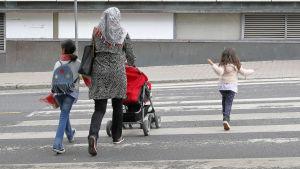 En kvinna med sjal på huvudet går med sina barn över en gata.