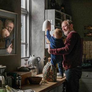 Karaktären Johannes står i ett mörkt kök och tittar skrattade på sitt barnbarn Anton.