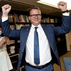 Petteri Orpo höger armarna och jublar i en segergest.