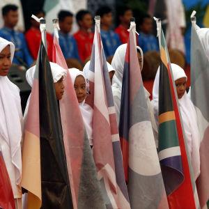 På en minnesstund i Aceh, Indonesien håller barn i de länders flaggor som landet fick hjälp av efter tsunamin.