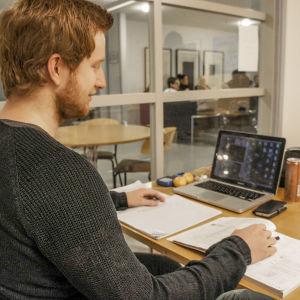 Högskolestuderande sitter vid ett bord med böcker och dator.