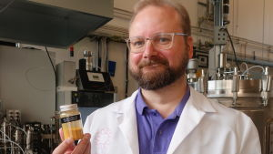 Juha-Pekka Pitkänen iklädd labbrock visar upp en burk proteinpulver.