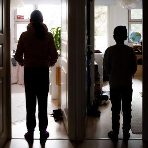 Kaksi lasta seisoo kahden huoneen oviaukoissa.