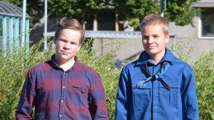 Två pojkar står bredvid varandra utomhus i solsken.