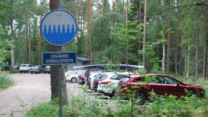 """Parkeringsplats med många bilar och en skylt med texten """"Liesjärvi kansallispuisto"""""""