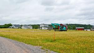En grusväg kantad av gräs och några enstaka hus samt en grävmaskin.