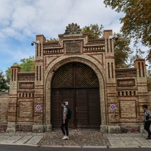 På bilden en stor synagoga byggd i ljust tegel. Framför byggnaden en man och en kvinna som går på en trottoar.