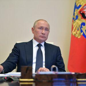 Man i blå kostym med slips ser in i kameran med neutral min. Bredvid honom står Rysslands flagga. Mannen är Rysslands president Vladimir Putin.