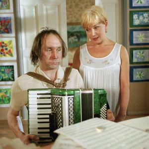 """Yleisradion televisio-ohjelma """"Maalaiskomedia: Mooseksen perintö"""". Näyttelijät Tom Lindholm (roolinimi Piiparinen) ja Katariina Kuisma (roolinimi Hellä Lehmus)."""