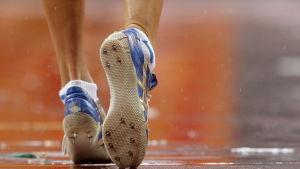 Löpare med skor på en blöt bana.