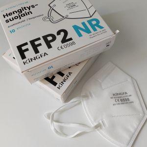 Kirurgisia hengityssuojaimia pakkauksessa ja yksi pöydällä.
