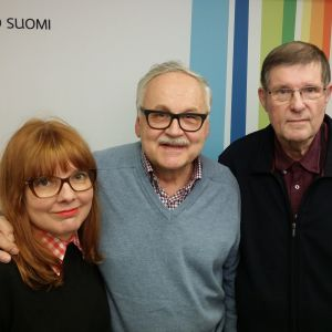 Susanna Vainiola, Ismo Sajakorpi ja Fredi seisovat Radio Suomen seinän edessä