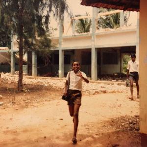 Hymyilevä nuori srilankalainen poika kävelee kohti kameraa koulun raunioiden edessä.