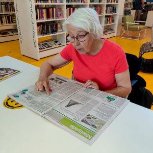 En dam i röd skjorta sitter vid ett bord i ett bibliotek och läser en tidning.
