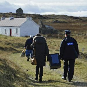 Polis och valförrättare bär på valurnan från ön Innishfree utanför Donegal. Två personer röstade.
