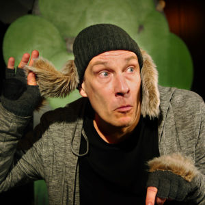 En skådespelare i grå rock och stora lurviga hundöron hängande från mössan, håller upp det ena örat med handen för att lyssna.