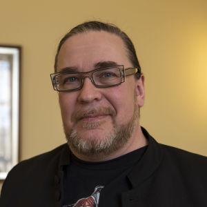 Politikern Jyrki Kasvi i närbild. Han har en svart t-skjorta och glasögon på sig.