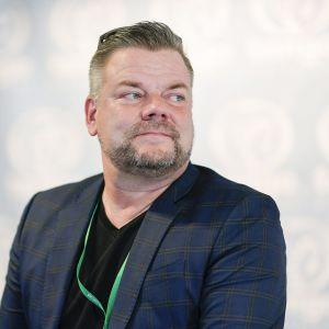Jari Sillanpää med blå kostym och skägg.