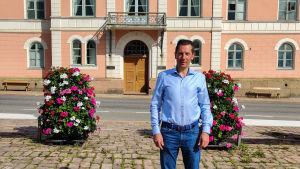 En man står framför ett rosa stenhus.