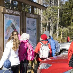 Människor står och läser vid en informationsskylt på ett friluftsområde.