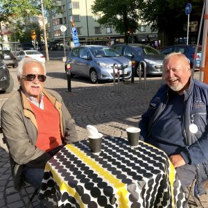 Två leende män sitter på ett torgcafé på Tölö torg.