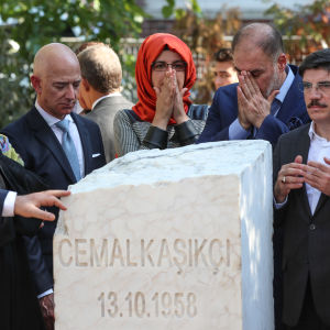 Viisi ihmistä seisoo valkoisen muistokiven takana.