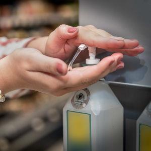 En kvinna pumpar ut handdesinficeringsmedel ur en pumpflaska.