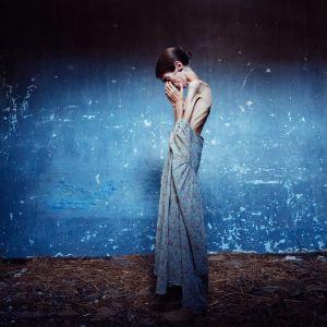 Hyvin laiha nainen seisoo sivuttain mekko valuen päältä, pitää käsiään kasvoillaan.