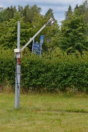 Ett mätinstrument i metall står på en gräsmatta. Mätinstrumentet ser ut som ett metallrör som det sticker ut ett annat metallrör ifrån.