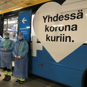 Coronabussen i Kråkkärret i Åbo, sjukvårdare med skyddsutrustning står utanför bussen.