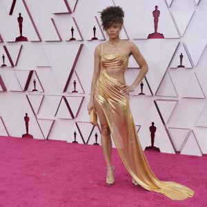 Skådespelaren Andra Day i guldklänning på röda mattan under Oscarsgalan 2021.