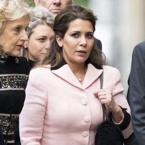 Kvinna iklädd rosa ser in i kameran. Hon omges av två kvinnor och en man. Kvinnan är jordaniens prinsessa Haya bint Al Hussein.