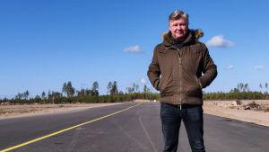 En man i dunjacka står på en landningsbana.