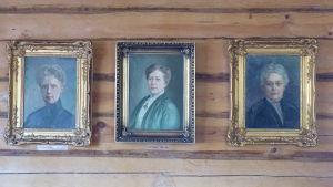 Tre porträtt på en brun stockvägg. Oljemålningar som föreställer tre kvinnor; Fanny Tavaststjerna, Cely Mechelin och Vera Hjelt