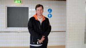 En man står utanför ett omklädningsrum i en simhall.
