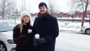 En ung Kvinna och en man står på Ågatan i Borgå. Det är snö på marken och de håller i var sin take away-mugg.