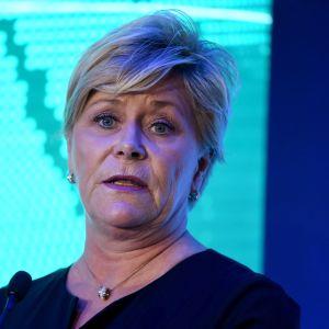 En blond, korthårig kvinna tittar framåt. Ljusblå och mörkblå bakgrund.