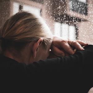 En kvinna lutar sitt huvud mot ett regnigt fönster.