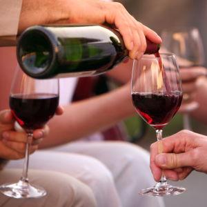 Rödvin hälls upp i glas.